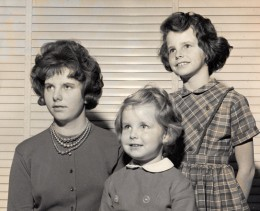 Me at twelve, standing behind my older and my younger sisters.