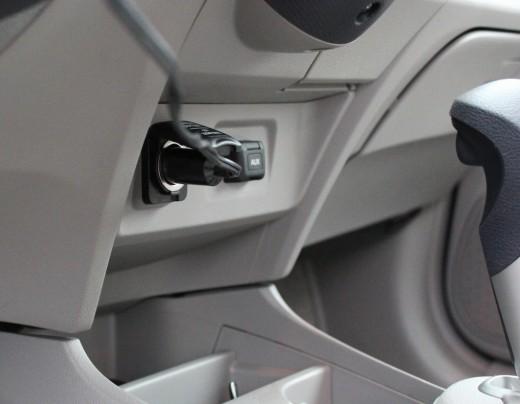 Air compressor plug inserted into 12V DC outlet.