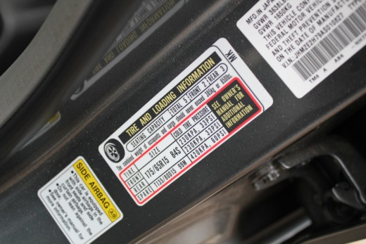 Tire pressure information label inside door frame panel.
