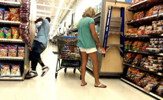 The unsuspecting shopper is simply going through the supermarket shelves, mind her own business and not aware that she is about to fall prey to falling - the latest internet fad