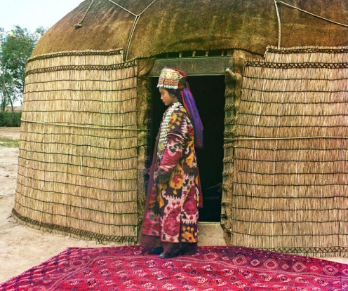 Full-length profile portrait of Turkman woman, standing on a carpet at the entrance to a yurt, dressed in traditional clothing and jewelry.
