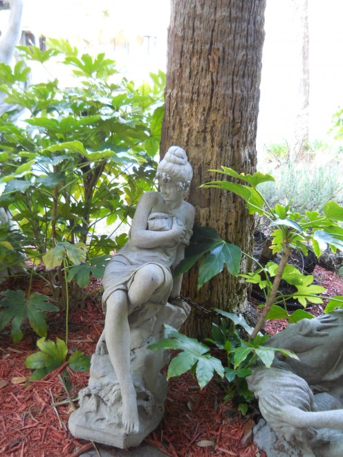Photo of a statue by a pond with water fountains.