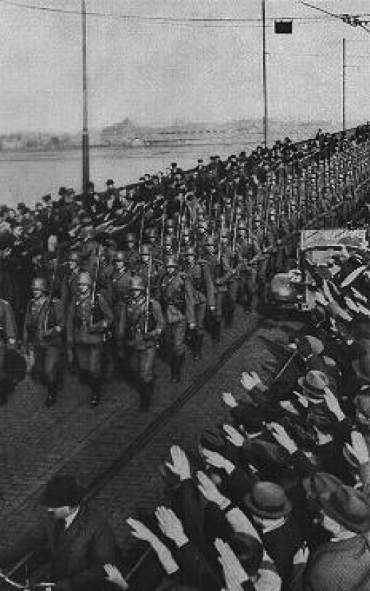 The Wehrmacht moves into the Rhineland during the remilitariztion of the area as German civilians look on.
