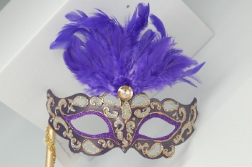 A Venetian-style mask with beribboned stick attached.
