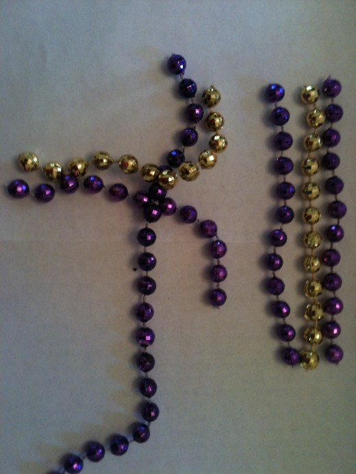 On the purple base, I began twisting with a 12 bead ball GOLD fringe piece.   Skip a BEAD BALL on the base.  Next came the PURPLE fringe piece.