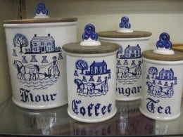 These Dutch inspired canisters are a mixture of ceramic and wood. Notice the intricate details that have been painted on the canister fronts.