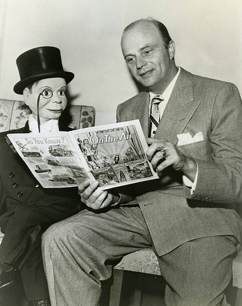 Photo of Edgar Bergen and Charlie McCarthy from NBC Radio. They are reading an NBC-produced comic book, On the Air, which told the story of what happens behind the scenes in radio broadcasts in a children's format.