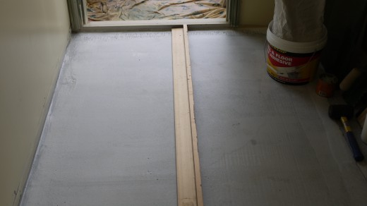 7 This is s long straight-edge recovered from a built-in-wardrobe. If you don't have a straight edge, then a string line will do, but don't hammer nails in the floor to anchor it because that will put a hole in the waterproof membrane.