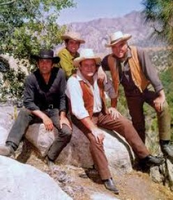 (FROM LEFT) ADAM, HOSS, BEN, AND LITTLE JOE POSE FOR PHOTO ON A ROCK THAT WAS ON THE PONDEROSA.