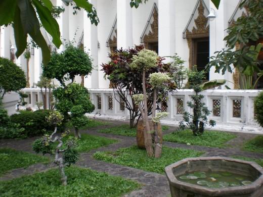 Tranquil interior garden. Wat Pho Buddhist Complex in Bangkok, Thailand.