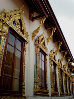 Exuberant, golden window frames enrich the Buddhist temple's architecture. Wat Phra Kaew, Bangkok, Thailand.