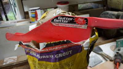 9. I found that a gutter-clearing plastic spade is ideal for getting grout out of the bag without generating a lot of dust.