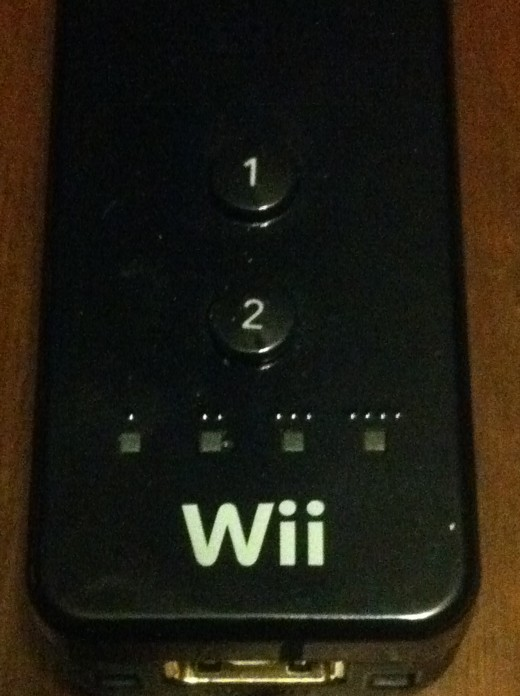 The four lights that correspond with your controller number are above the Wii logo on the front of the Wii Remote.