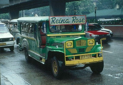 A loaded, fully-decorated jeepney in traffic.