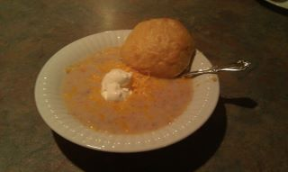 served with a roll for dipping, topped with cheddar cheese shreds and sour cream