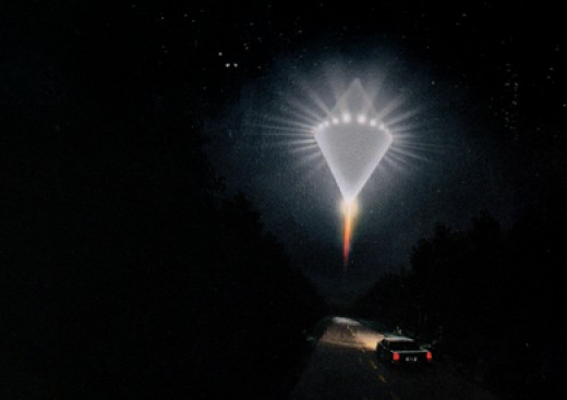 """The light emanated from a diamond shaped craft that hovered above the trees, below it expelled a massive flame that produced and extreme amount of heat. """