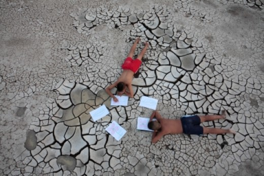 Two children drawing on dry land.
