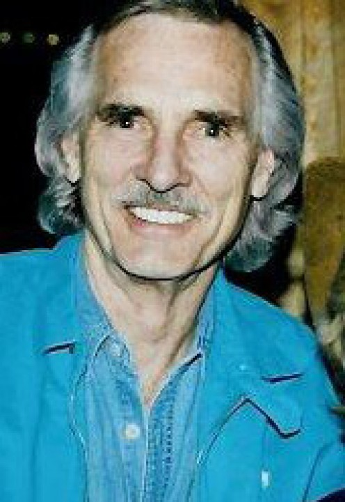 "DENNIS WEAVER AS ""CHESTER,"" IN A RARE CAMEO APPEARANCE. HIS INTERVIEW WITH HOLLYWOOD MAGAZINES ABOUT HIM RETIRING OUT OF FEAR OF GUNS, WAS NEVER PUBLISHED."