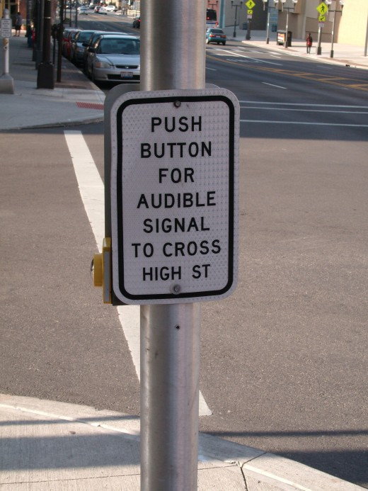 I had to really think about this one for a bit. If you need to push the button for an audible signal, because you can't see (therefore need to hear when it's okay to cross)...how can you see (read) the sign in order to find the button?