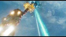 Iron Man in flight fighting alien forces as he heads to what looks like a rip in the sky