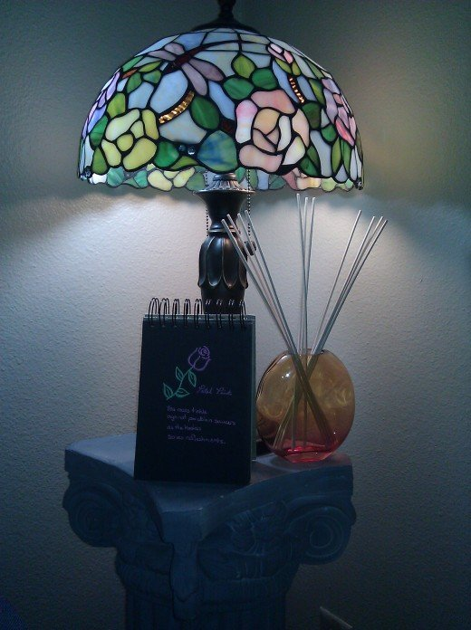 This pillar positioned in one corner of my living room features a Tiffany lamp I found on clearance, a flip book with some of my own artwork, and a fragrance diffuser.