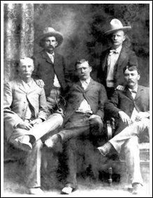 "Barney Riggs in 1902. Standing: BrotherTom Riggs on left, Lon ""Stump"" Robbins on right. Seated, left to right: Moye Grinder, Barney and John Chalk"