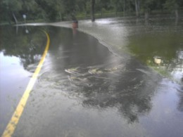 Flood waters washing over a roadway frequently move along with a current that could easily wash a car away.