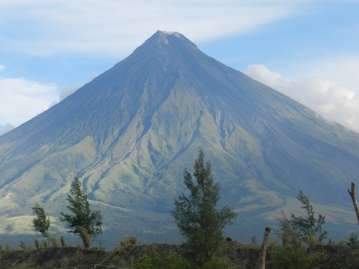 The sun shining down as it rises next to the awesome force of the Mayon Volcano