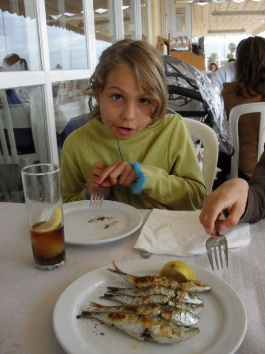 Girl trying grilled sardines for the first time.  Guess what?  She loved them!