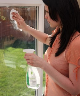 A young woman using vinegar to clean limescale from an outside window. The limescale is removed effortlessly with vinegar