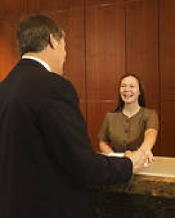 SEE THE SMILING FRONT DESK CLERK? A SMILE GOES A LONG WAY WITH ANY ROAD-WEARY TRAVELER.
