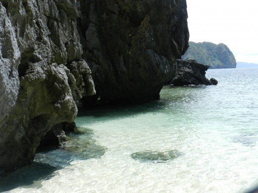 More volcanic style cliffs set themselves on crystal clear waters set next to white sand beaches lined with coconut trees.