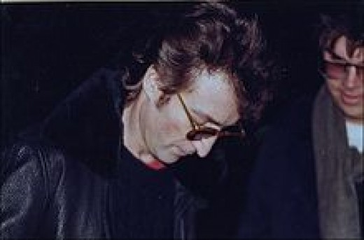 a photo of John autographing for Chapman hours before his murder