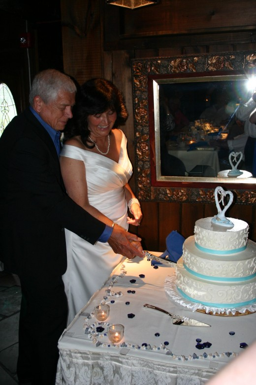 Cutting the wedding cake, which was included in the cost of the meal. The decorations on the table were bought for $1.99 per package at the Christmas Tree Shops and added a lot of color to the cake table and the reception tables.