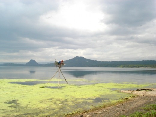 a local sitting on top of a makeshift stickstand shooting some fish at the Lake Taal, Volcano overhead...