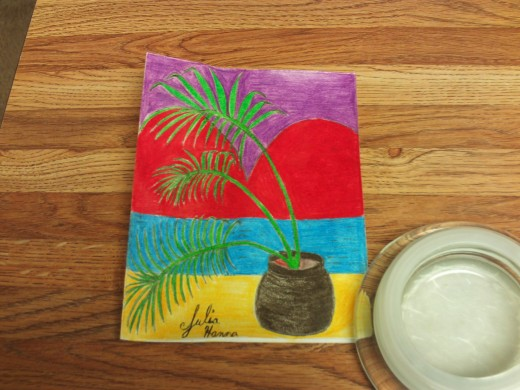 A chrome colored pencil was used to color in the deck where the palm tree is standing.