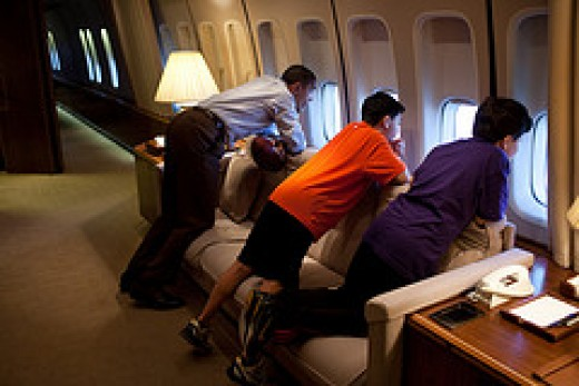 President Obama (in white shirt) and friends gaze out the window of Air Force One. What a view that must be.