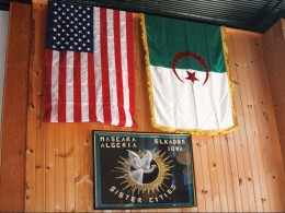 American and Algerian flags hang on the wall of Sheha's Cafe in Elkader, Iowa, above artwork celebrating the sister-city relationship between Elkader and Abd el-Kader's birthplace: Mascara, Algeria.
