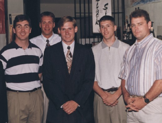 Erik - the blonde male in the center, wearing a black suit. This is how he looked before surgery.