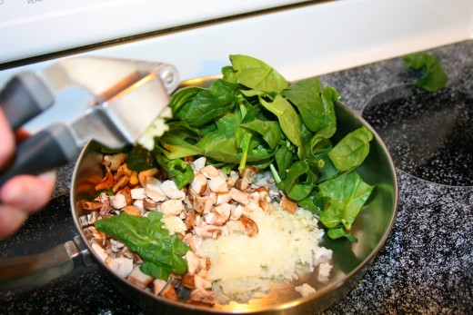 Add the olive oil, spinach, onions, garlic, and mushrooms to a skillet.