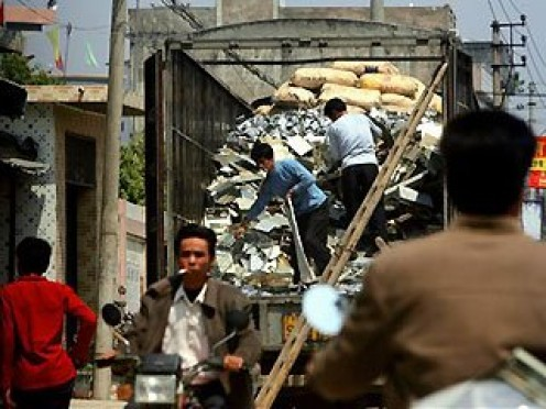 March 16, 2006: Workers unload electronic waste from trucks as seen from a hidden position inside of a vehicle in Guiyu, China.