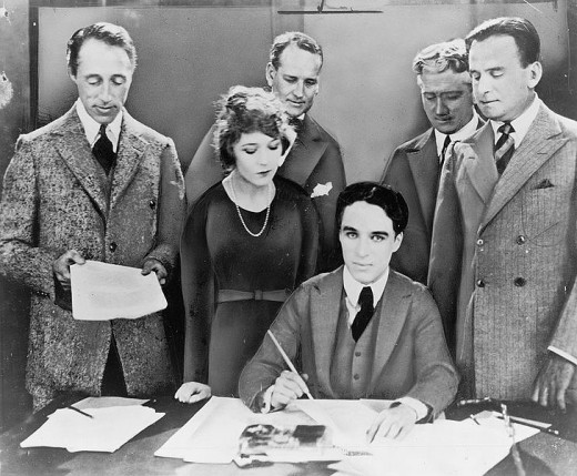 D.W. Griffith, (front left) Mary Pickford, (front center) Charlie Chaplin, (seated) and Douglas Fairbanks (front right)  sign a contract to start United Artists studios.