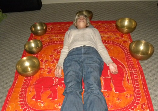 The client lies on the floor with the bowls arranged around her in a semicircle.