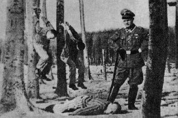 Guard at Buchenwald poses with his victims