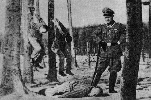 Guard at Buchenwald poses with his victims