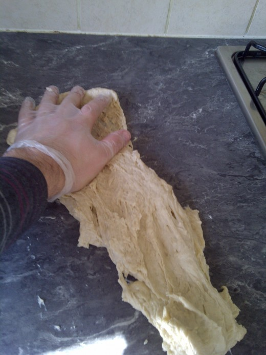 After you get to this point and you've stretched the dough in one fluid motion, roll it back up, turn the dough (so you knead evenly) and repeat for about 10 minutes! And don't worry about the little flecks of dough you leave behind!
