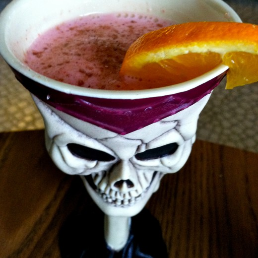 Jack's smoothie topped with cinnamon/sugar topping in a skull goblet and garnished with an orange slice