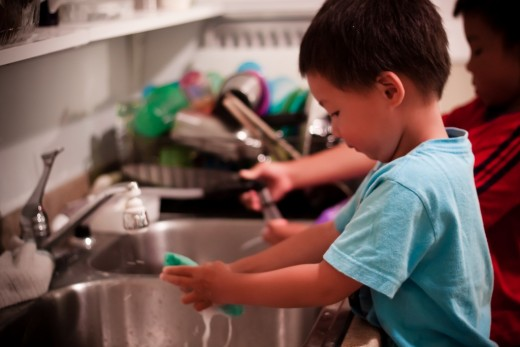 young child washes the dishes