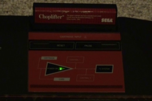 A green triangle appears beneath where you insert the game cartridge and above where the card slot is located.