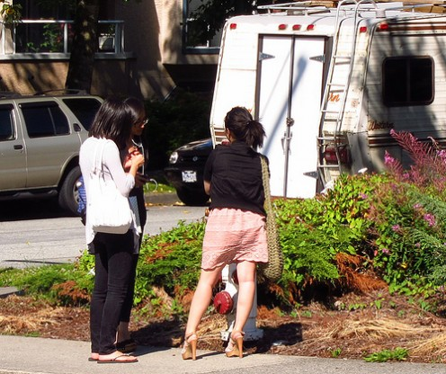 THESE GIRLS ARE AMAZED AT SOMEONE'S CARELESS PARKING BEHAVIOR--PARKING TOO CLOSE TO A FIRE HYDRANT.